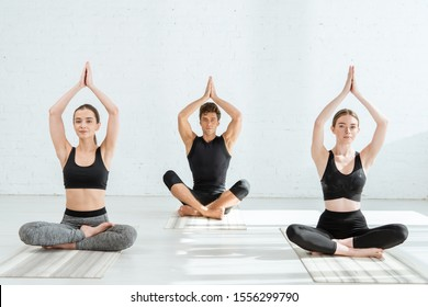 young women and man practicing yoga in half lotus pose with raised prayer hands