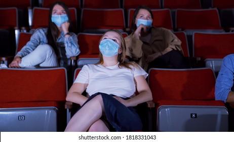 Des jeunes femmes en masques regardent un film au cinéma. Médias. Regarder des films dans les cinémas dans le contexte de la pandémie de coronavirus. Des gens s'assoient sur des masques de protection assis dans un cinéma