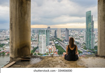 Young women meditates in yoga position on high building. Unique concept of meditation, spirituality and balance.