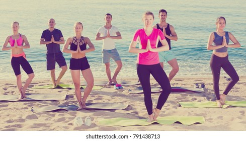 Young women and men exercising yoga poses on sunny beach by ocean