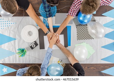 Young women and men keeping baloons and putting their hands together