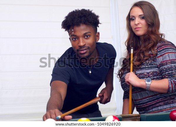 young women and men playing pool billiards fun activity recreation bar ball game