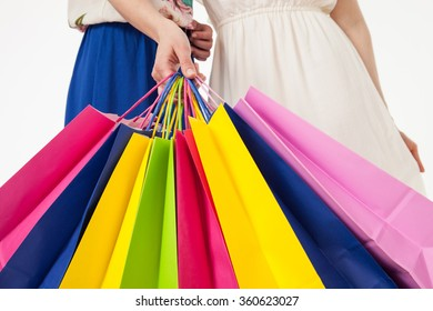 Young women with multicolored shopping bags, closeup shot on white background