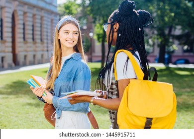 Young women multiethnic friends walking talking at university during break. Two high school girls with books, conspects outdoors in campus. Different races women friendship concept.