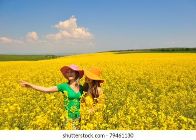 young women on blooming rapeseed field in summer