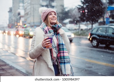 Young women on city street enjoy in snow fall, she hrinking smoothie