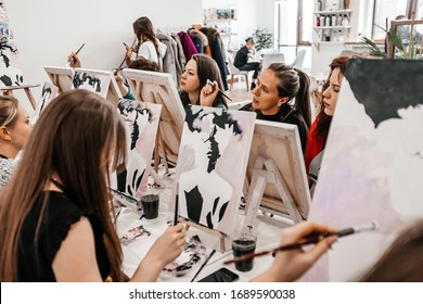 Young women paint with brushes on easels in art class. art school, creativity and people concept