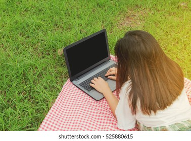 Young women in the park, she is working with a notebook
