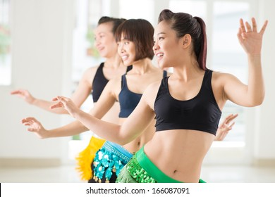Young women performing belly dance in a dance studio on the foreground
