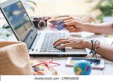 Young women planning summer vacation trip and searching information or booking hotel and using credit card on laptop, Travel concept