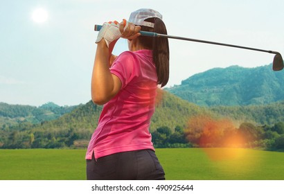 Young women player golf swing hit shot on course in summer and lens flare
