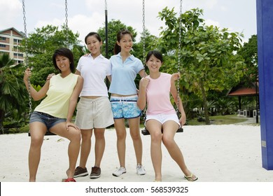Young women in playground, sitting on swings, smiling at camera
