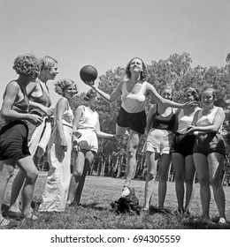 Young women playing with ball on summer day