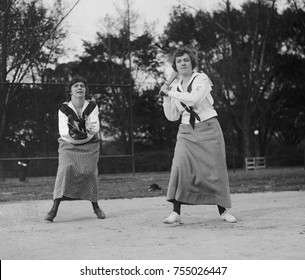 Young women playing baseball in middy shirts and long skirts in 1919. Washington, D.C.