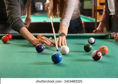 Young women playing billiard in club