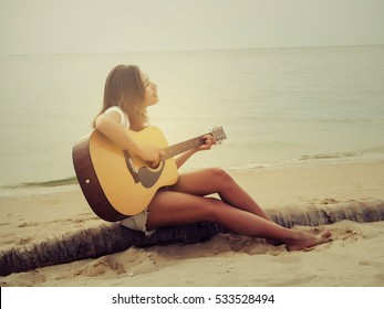 Young women playing guitar on the beach.