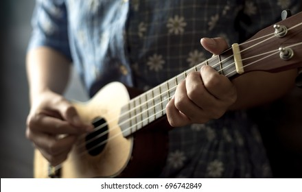 young women playing on ukulele in close up view