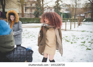 young women playing in park with snow cover and moving – energy, cheerful, interaction