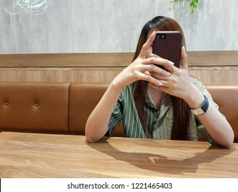 young women playing smartphones in the cafe