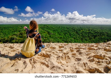 Young women pointing finger on top of a sand dune in Arcachon, France