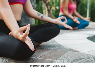 Young women practicing yoga during luxury yoga retreat in Asia, Bali, meditation, relaxation, getting fit, enlightening, green grass jungle background