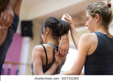 Young women practicing yoga at the gym and stretching their arms, the instructor is helping them
