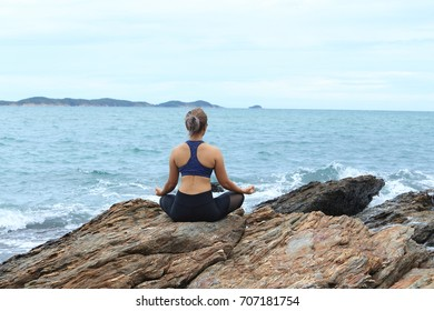 Young women practicing yoga on the rocks. on the beach.