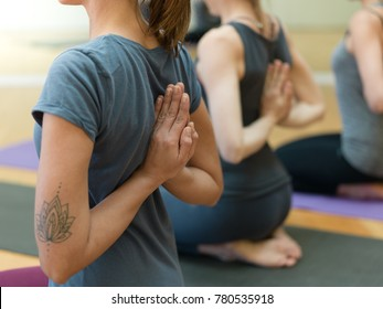 Young women practicing yoga together, they are doing the reverse prayer pose and clasping their hands behind their back