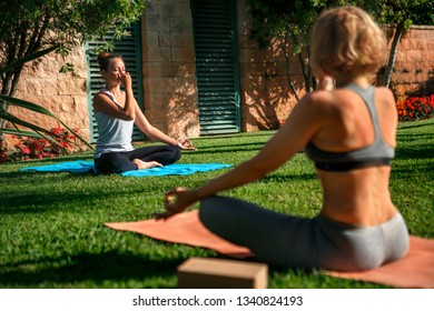 Young women practising pose under control of female yoga teacher outdoors