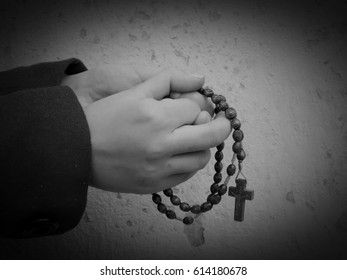 Young women praying with rosary in the palms