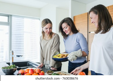 Young women preparing some tasty food in the modern kitchen. Woman holding patato with meat dish