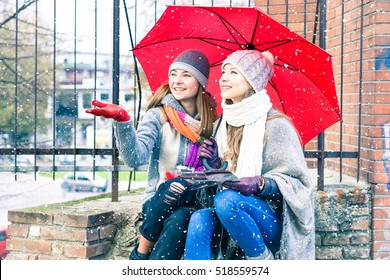 Young women reaching snowflakes under red umbrella at winter holiday - Happy female friends sitting at street corner holding city tour map looking up at snowy weather - Forecast and vacation concept