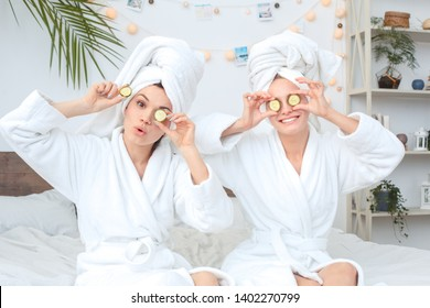 Young women rest together at home beauty care wearing bath robes sitting on bed covering eyes with cucumber slices looking camera smiling playful