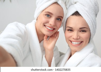 Young women rest together at home beauty care sitting on sofa wearing towels taking selfie photos on smartphone looking camera smiling happy close-up