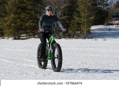 Young women rider winter cycling on a fat bike on a lake