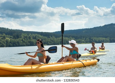Young women rowing on kayaks with friends summertime