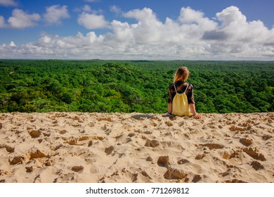 Young women setting on top of Dune of Pilat in Arcachon, France