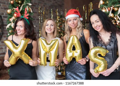 Young women showing word xmas made of golden helium balloons