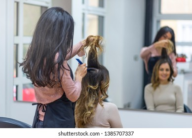 Young women sitting in beauty hair salon style. Situation in a Hair salon. Beautiful hairstyle of young woman after dying hair and making highlights in hair salon.