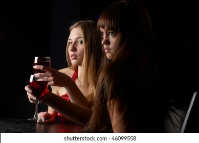 Young women sitting in cafe with wine an? talking