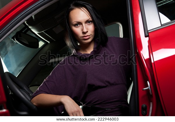 Young women sitting in modern red car
