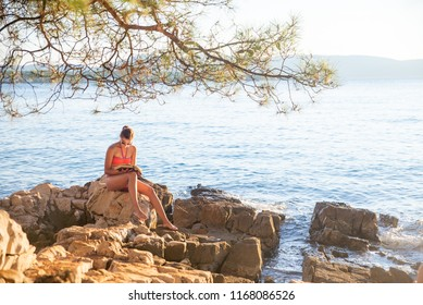 Young women sitting on a beach relaxing with book. Blue sea in the background. Summer vacation concept.  Woman on a beach near Malinska on Island Krk.