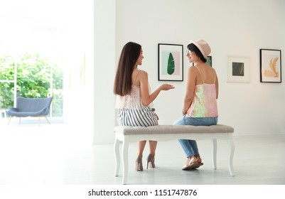 Young women sitting on bench at exhibition in art gallery