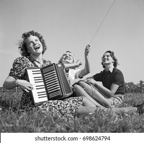 Young women sitting on grass and playing accordion
