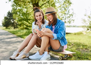 Young women sitting on longboard using phone and drinking lemonade