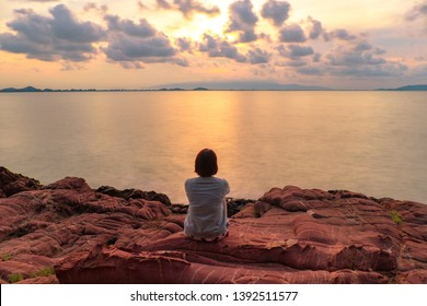 Young women sitting on pink stone (Arkose) near Kung Krabaen Wildlife Reserve in the morning in Chantaburi province of Thailand