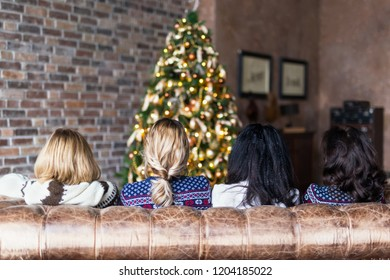 Young women sitting on the sofa near decorated Christmas tree in cozy loft. Rear view
