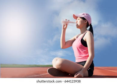 Young women sitting on sport track drinking water