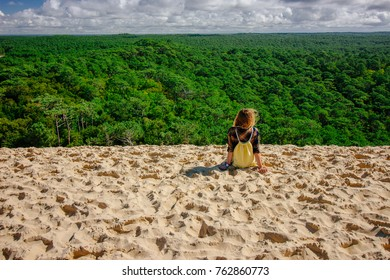 Young women sitting on top of the Dune of Pilat sand dune looking over pine tree forest in Arcachon, France