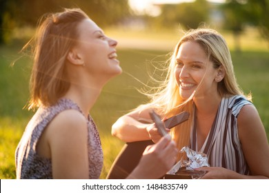 Young women sitting together in park with bars of chocolate